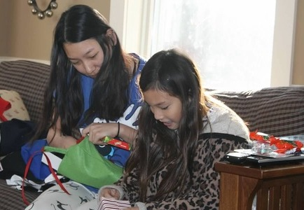 big sister and little sister opening Christmas gifts together