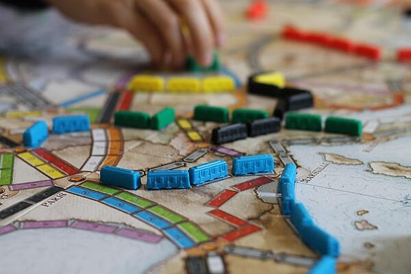 plastic train car tokens linked across a Ticket to Ride game board