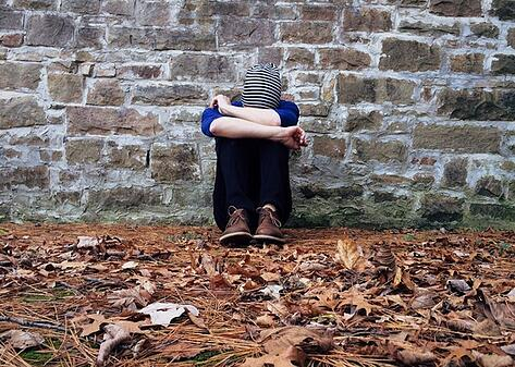 boy sitting against a wall with head in hands to illustrate culture shock symptoms and emotions