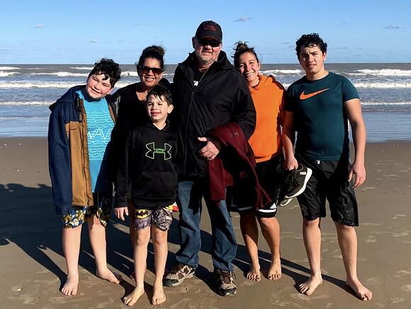 Vanessa and host family on the beach with ocean behind