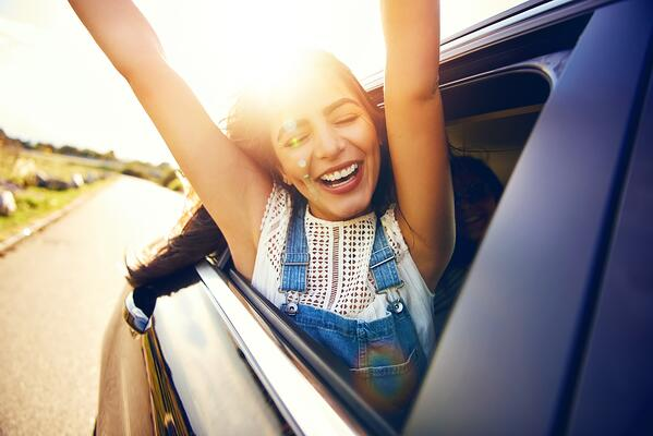 happy girl with arms out car window