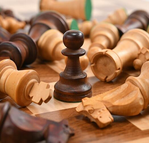 chess pieces knocked over with one standing