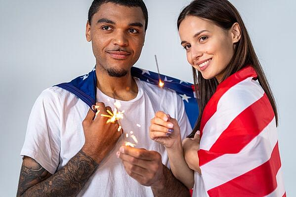 couple wrapped in american flag holding sparklers