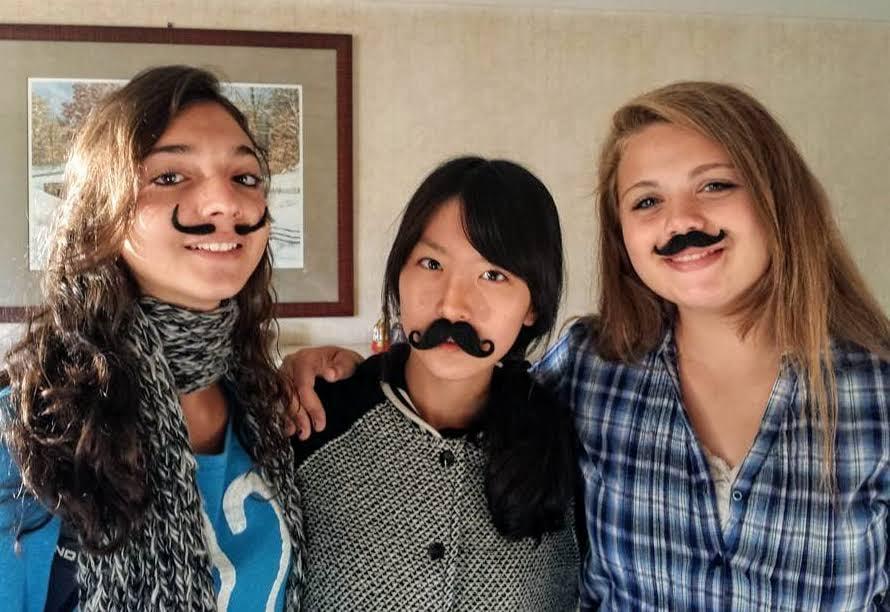 three smiling teenage girls with fun, fake moustaches