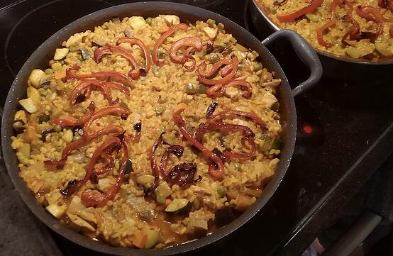 A creative paella with a mix of vegetables and meat topped with red peppers