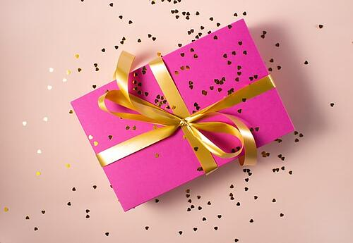 a package wrapped in pink paper with gold ribbon and glitter