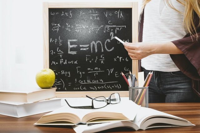 student pointing chalk to blackboard showing E=mc2 and math formulas