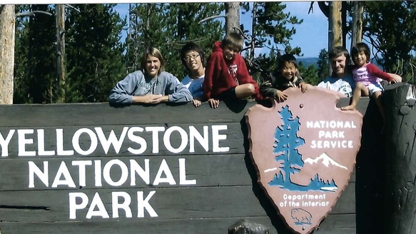 family photo with Yellowstone National Park sign