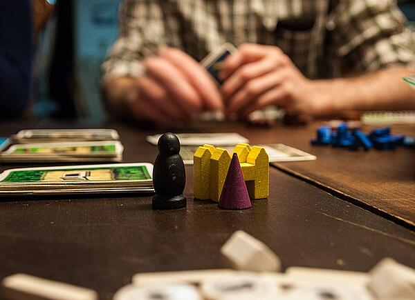game player holding cards with wooden tokens on the board
