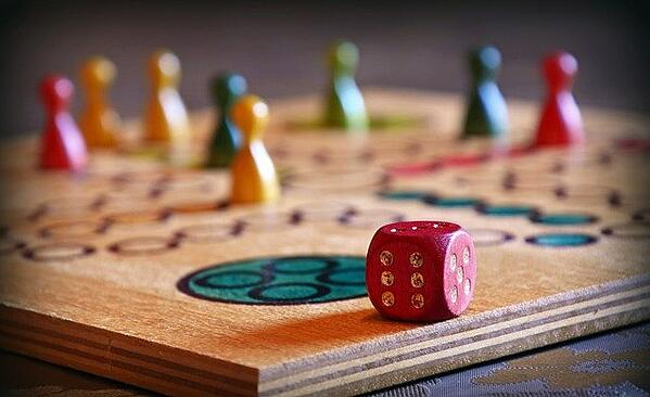 colored tokens and a red die on a wooden game board