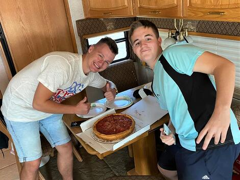 boys smiling with deep dish pizza