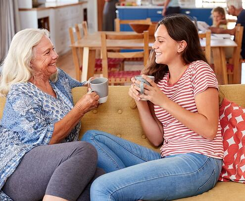 teen girl on couch with senior woman drinking coffee together