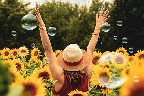 happy girl raising both arms to the sky in a sunflower field to illustrate cultural adaptation and overcoming culture shock