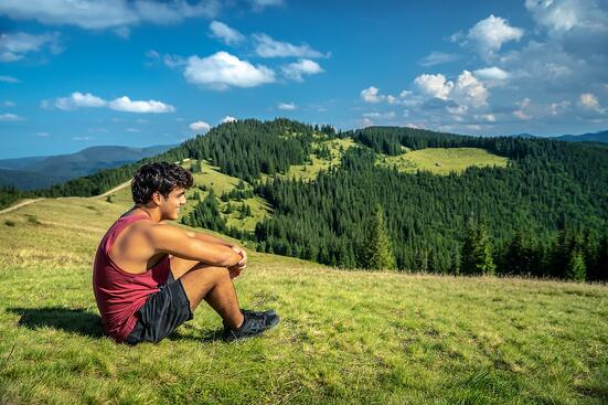 teen boy sitting in grass enjoying beautiful mountain view