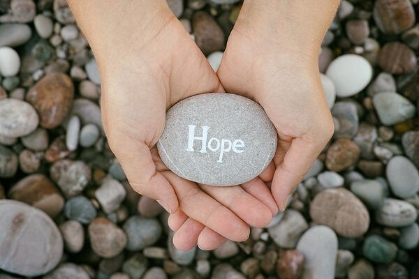 "hands holding rock that says ""hope"""