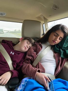 A Spanish exchange student and her host brother sleeping in the car