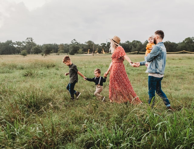 a mother, father and small children walking through a field