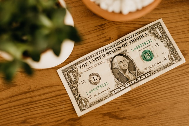 a US one dollar bill laying on a wood table