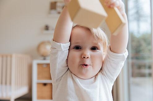 baby raising hands above head
