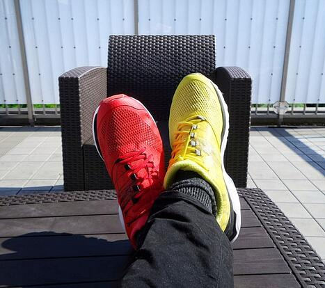 male feet wearing two different colored shoes