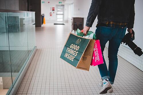 man with two shopping bags at mall
