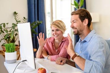 couple waving at computer