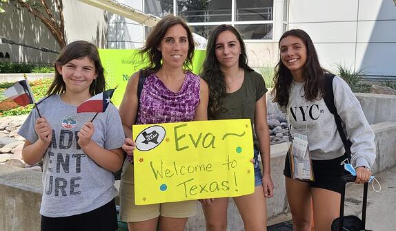 mother and two daughters welcome exchange student with a yellow welcome sign