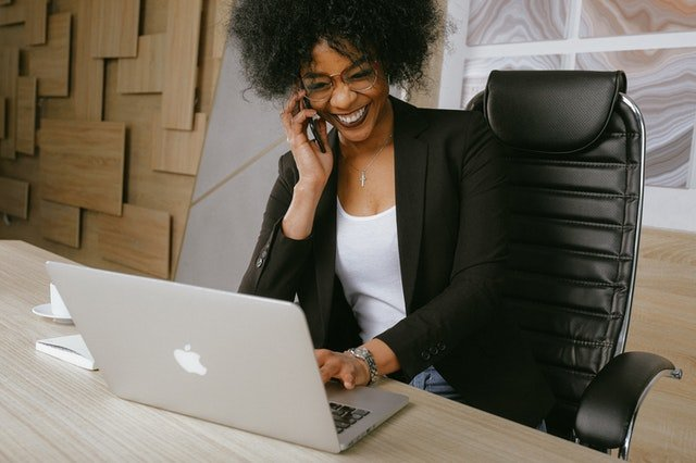 a woman of color smiling and talking on the phone while working on computer
