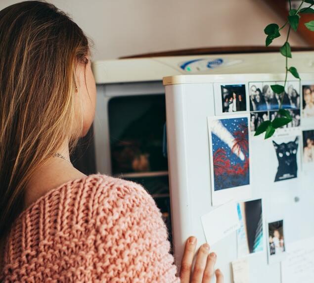 teenage girl opening fridge looking inside