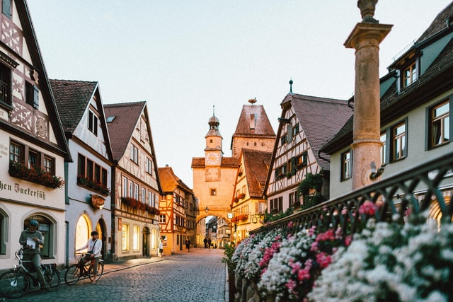 a cobblestone street in Germany lined with traditional shops and houses