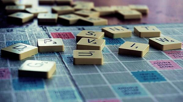 scrabble tiles scattered on the game board