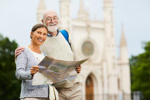 senior couple holding map in front of castle