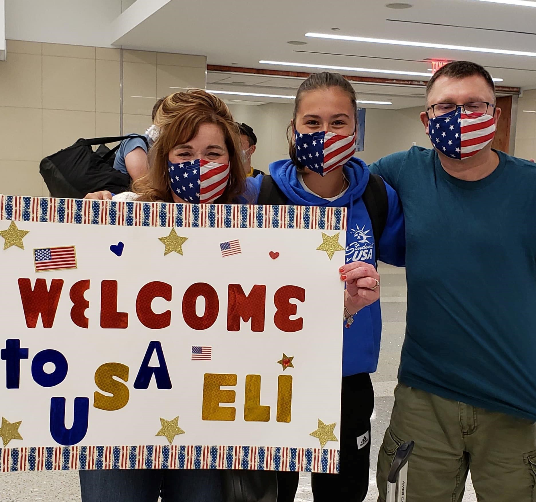 family wearing masks at the airport holding welcome sign for exchange student