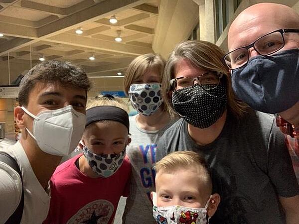 host family waiting for exchange student at the airport wearing masks during the pandemic