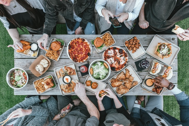 family picnic with a buffet of burgers, chicken and pizza
