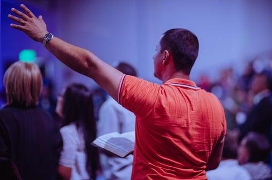 man worshipping at church