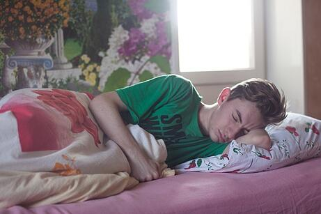teenage boy in bed to illustrate culture shock symptoms