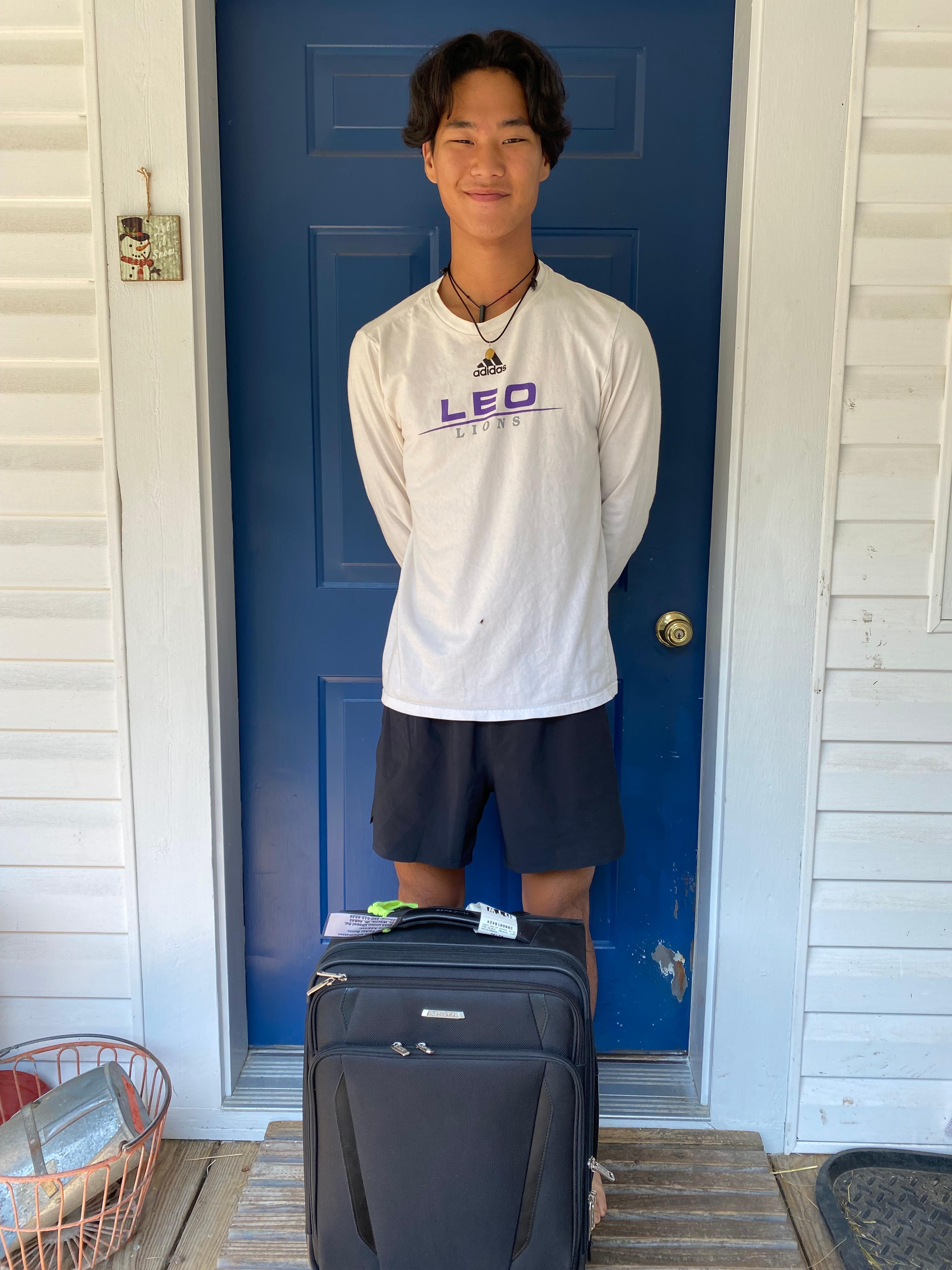 teenage boy with suitcase standing in front of door