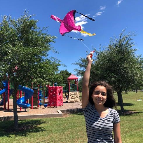 teenage girl flying pink bird kite