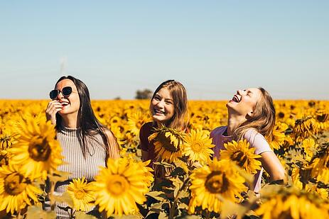 teenage girls smiling in sunflower field showing cultural adaptation and overcoming culture shock and transition stress