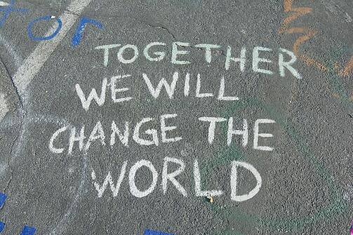 """together we will """"change the world"""" written in chalk on the street"""