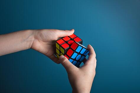 two hands working on rubics cube to illustrate understanding culture shock