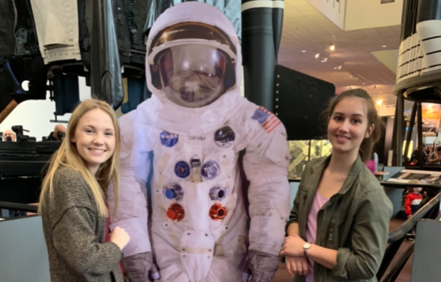 two teenage girls with astronaut mannequin at aerospace museum