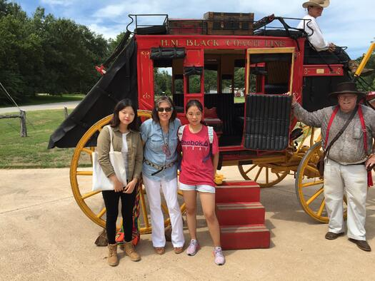 woman and two girls in front of a stagecoach