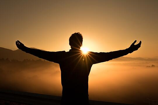 young man standing with arms wide open looking at the sunset