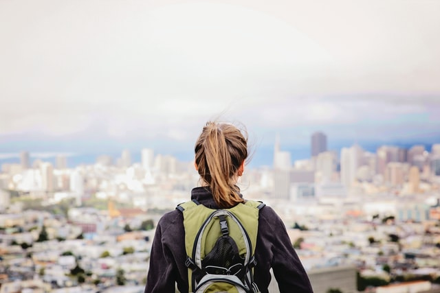 young woman standing alone looking at a city scape